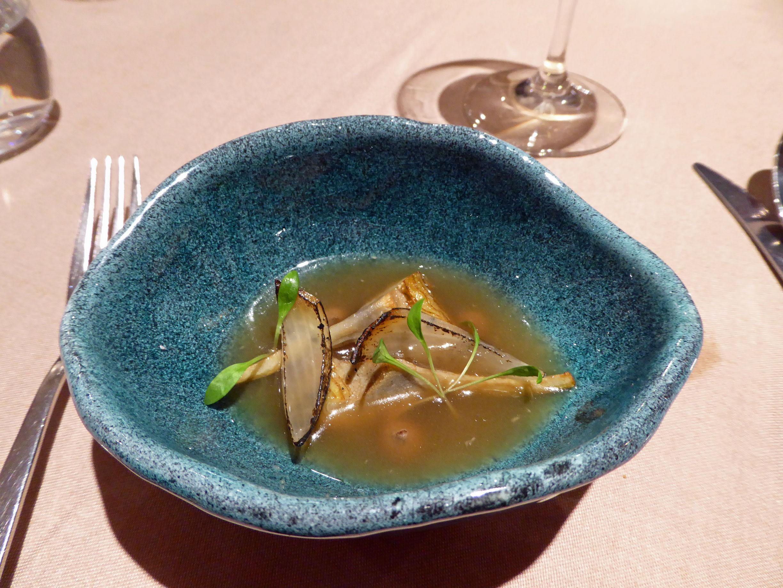 Restaurante en Barcelona Alcachofa confitada con cebolla escalibada, puré de ajo negro y caldo de jengibre