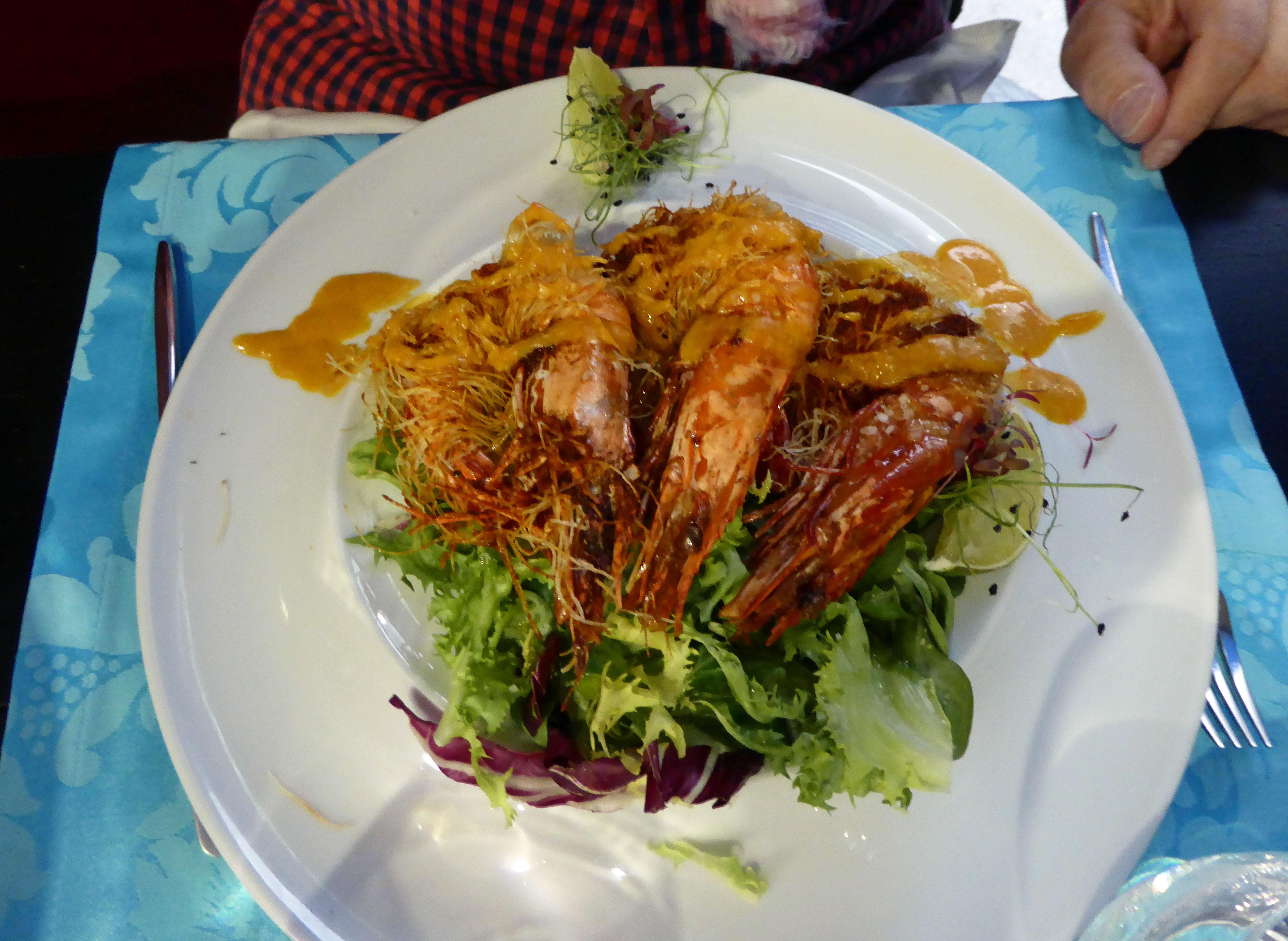 Restaurante en Oporto Gambas rebozadas con pasta filo, salsa de mani y de coco, sobre un fondo de ensalada verde