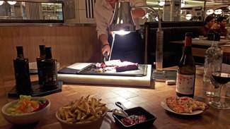 Acompañamientos (pimientos del piquillo confitados, patatas fritas caseras, ensalada verde)  y lámpara térmica para mantener la carne a su buena temperatura