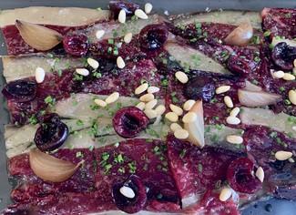Lascas de vacuno curado con cebolla encurtida, piñones y cerezas